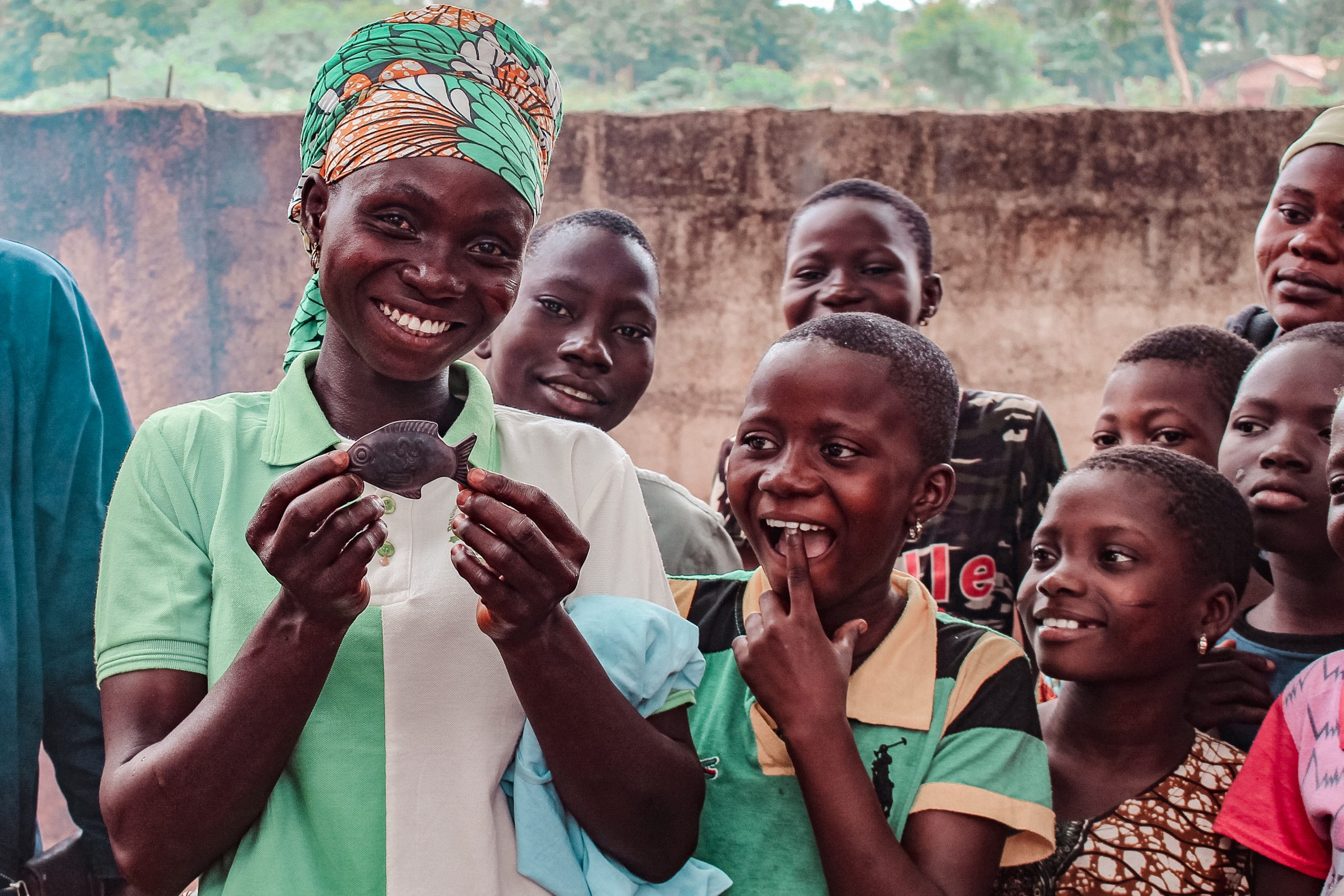 Smiling women and children while working with CARE in Benin