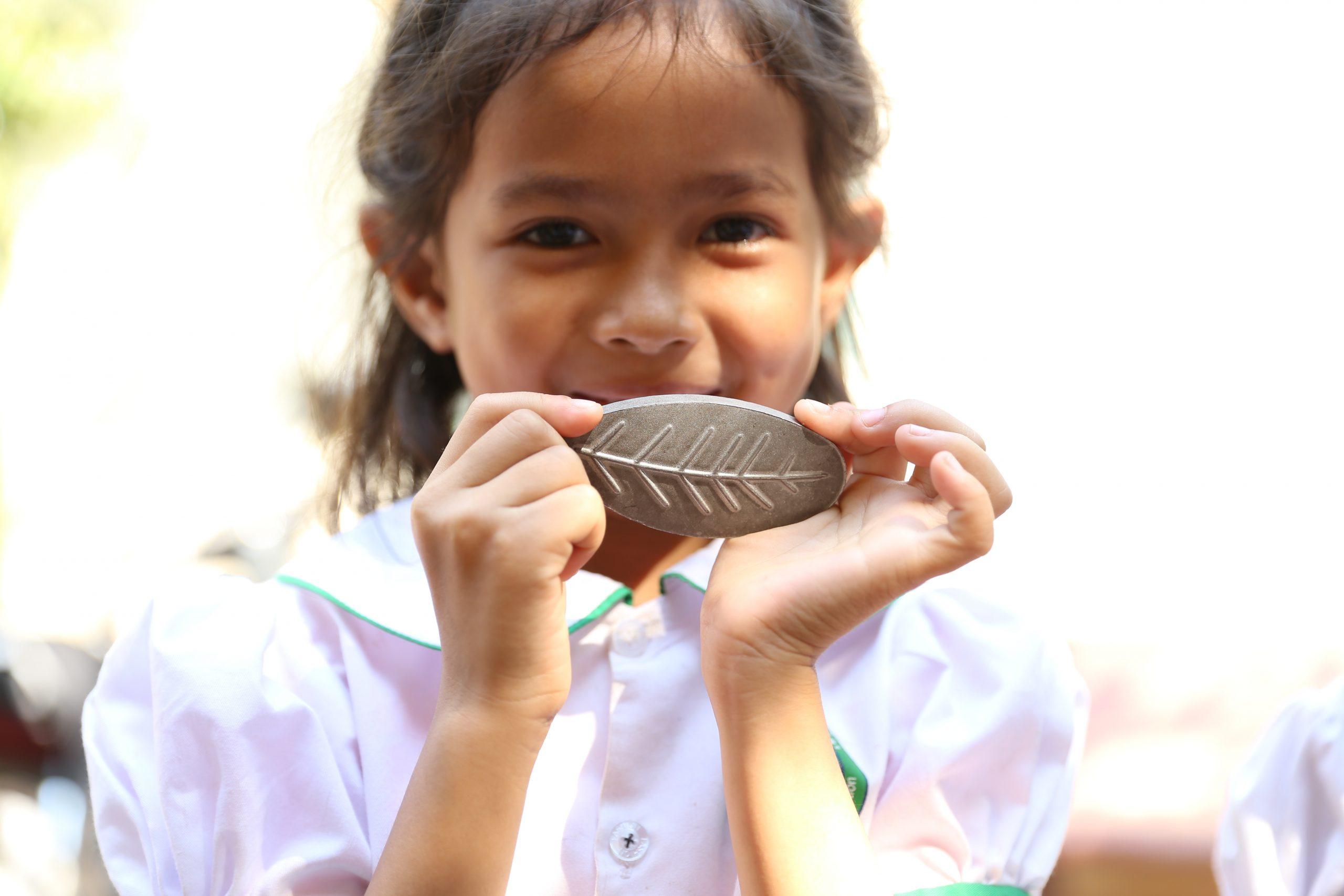 Smiling girl holding Lucky Iron Leaf in Cambodia